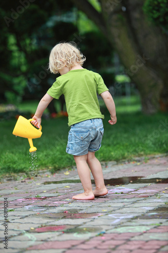 White little barefoot girl playing with water can