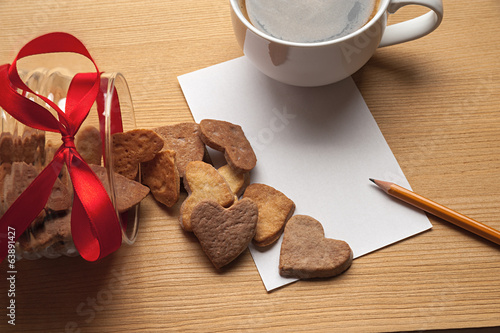 The cup of coffee on the table with a piece cookie