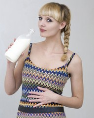 Woman holds in hand a plastic bottle with milk