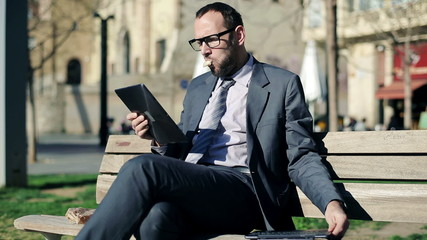 Young businessman with tablet computer sitting on bench in the c