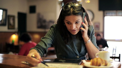 Angry businesswoman talking on cellphone by the counter in bar