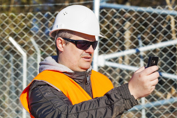 Engineer with the cell phone near to the fence