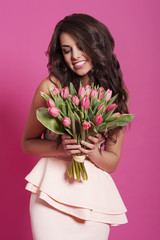 Natural smiling woman with bouquet of fresh tulips