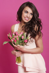 Beautiful young woman posing with pink tulips