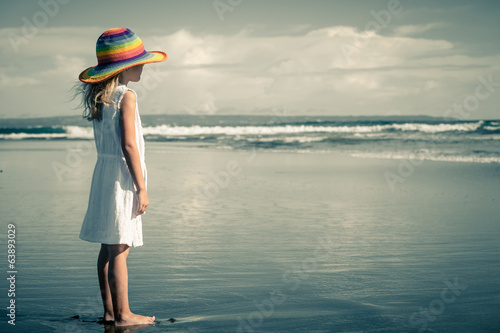 Sad little girl standing at the beach in the day time