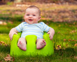 Happy infant baby boy using training seat