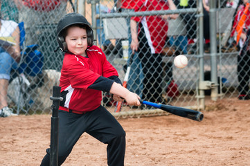 Young baseball player hitting ball off a tee during game