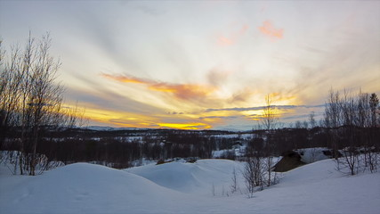 Panorama sunset over the snow-covered hills