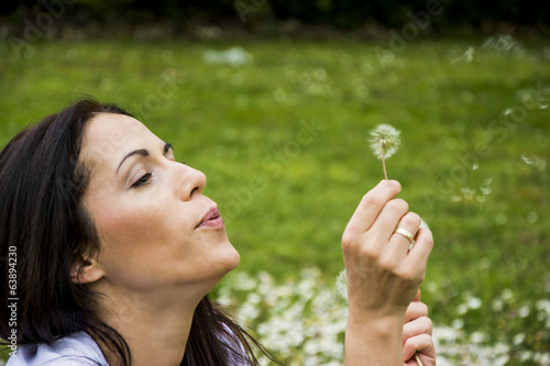 Young woman blowing dandelion on a field