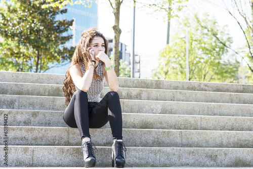 Pensive young woman talking by phone and sitting on stairs.