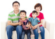 happy asian  family sitting on a white leather sofa