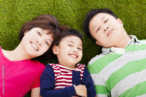 happy parents and son lying on a meadow