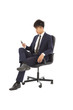 Young businessman sitting in a chair and watching smartphone