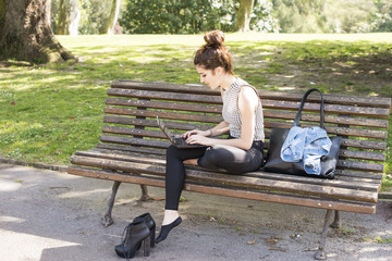 Young woman relaxing and laptop in the park.