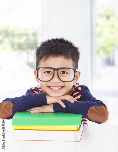 smiling little boy lying on books