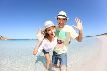 Happy couple walking in crystal clear sea water