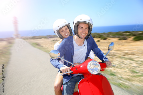 Cheerful couple riding red moto on island
