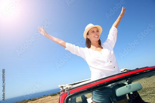 Smiling girl in convertible car showing arms up