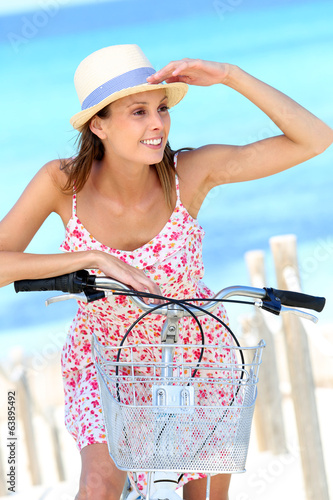 Attractive young woman riding bicycle by the beach