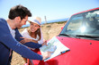 Couple looking at road map on red car hood
