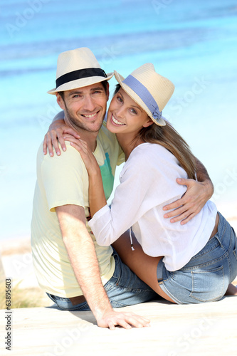 Couple on vacation sitting by the beach