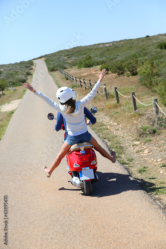 Back view of couple riding moto in natural landscape
