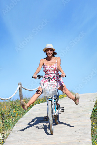 Girl with summer dress riding bicycle by the beach