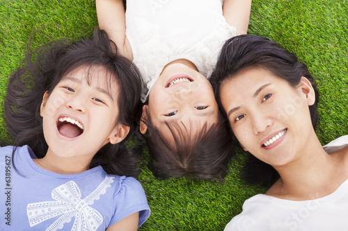 happy mother and daughters lying on a meadow