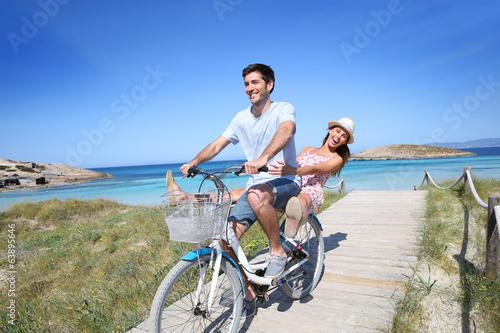 Man giving bike ride to girlfriend on beautiful Island - 63895646