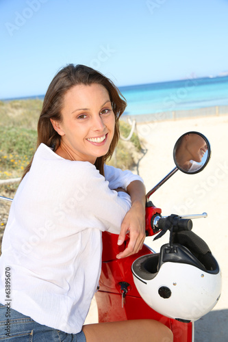 Smiling girl sitting on red scooter by the beach