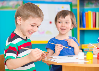 Cute children drawing with colorful paints at kindergarten