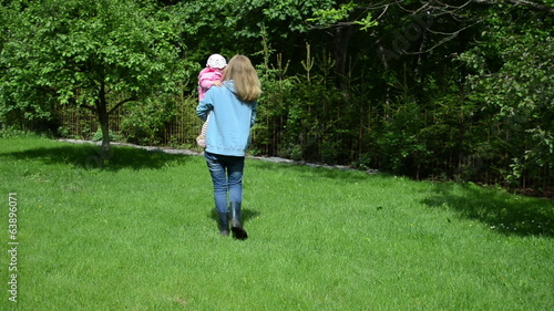 nanny have fun with little girl in garden takes child on hand
