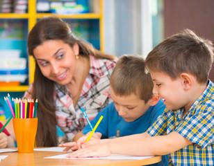 Happy children drawing at kindergarten
