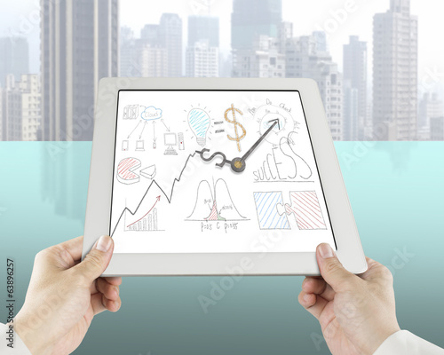 Holding tablet with business concept drawing and clock hands