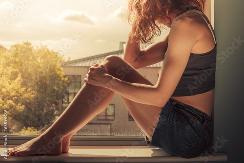 Young woman sitting on window sill on sunny day
