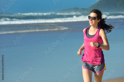 Woman running on beach, beautiful girl runner jogging outdoors