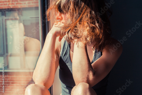 Young woman sitting in window and thinking