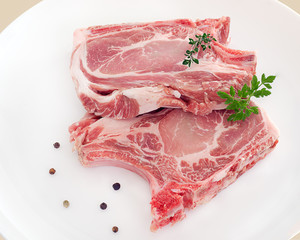 côtelettes de porc cru sur assiette