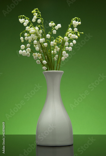 Lily of the valley  in flower pot on gradient blue background