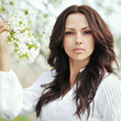 Beautiful young brunette woman standing near the apple tree - cl