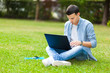 canvas print picture - Student using a laptop on the grass
