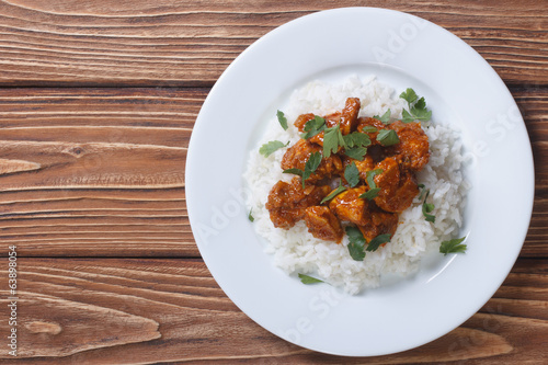 Chicken curry with rice and cilantro on a plate top view