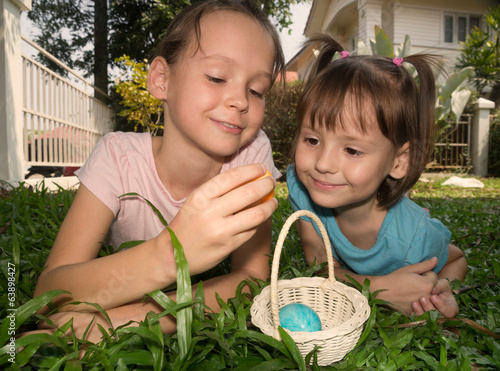 girls find easter egg and put in basket
