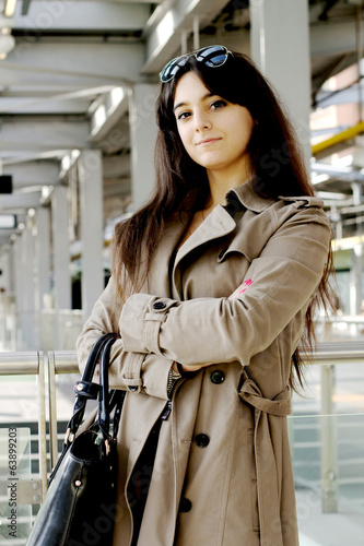 satisfied young businesswoman against industrial background