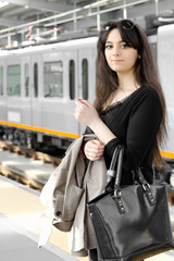 YOUNG BUSINESSWOMAN WAITING FOR THE TRAIN