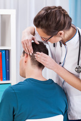 Young doctor examining patient