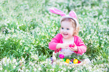 Beautiful toddler girl in bunny ears playing with Easter eggss