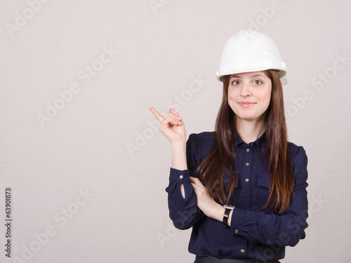 Woman engineer in helmet points finger to right