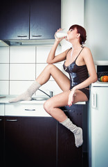 Sexy woman in shirt and socks drinking milk in kitchen