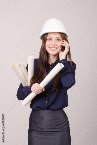 Girl a helmet talking on phone with blueprints in hand